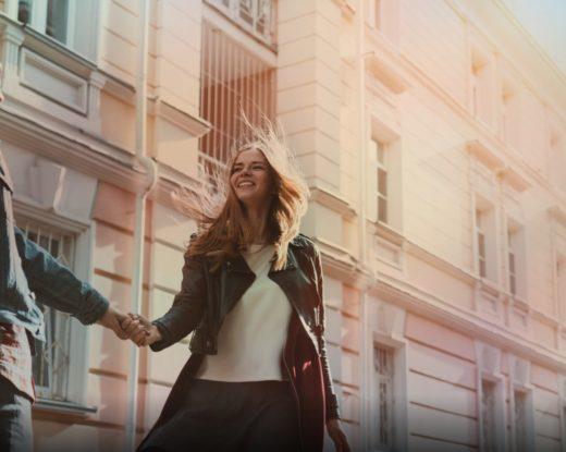 Couple qui se sourit et se tient la main dans la rue